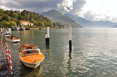 Vista do lago Como em um dia nebuloso com barco a motor e do porto em Bellagio Fotografia de Stock