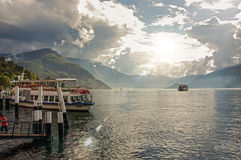 Vista do lago Como em um dia nebuloso com barco a motor e do porto em Bellagio Imagens de Stock Royalty Free