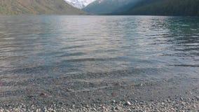 Vista do lago de montanha da costa rochosa A praia de um lago de montanha vídeos de arquivo