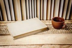Vista do livro e de um copo do chá na prateleira Fotos de Stock Royalty Free