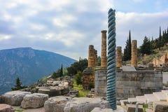 Vista do local da montanha de Delphi Greece antigo com a coluna torcida na frente do templo de Apollo com um Tesouraria abaixo do imagem de stock royalty free