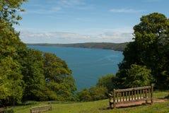 Vista do mar através das árvores com o banco no primeiro plano Imagem de Stock Royalty Free