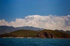 vista do mar montanhoso dos azuis celestes das ilhas contra nuvens de cúmulo do céu azul foto de stock