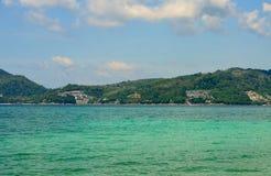 A vista do mar, o céu e as montanhas cobertos de vegetação com a selva tri Trang encalham em Phuket Foto de Stock