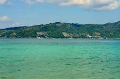 A vista do mar, o céu e as montanhas cobertos de vegetação com a selva tri Trang encalham em Phuket Fotos de Stock