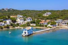 Vista do mar a uma cidade pequena em barcos menores, amarrados de Balearis, em barcos e em iate, e em uma casa pequena no cais na foto de stock
