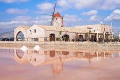 Vista do moinho de vento nas bandejas de sal, Trapani Sicília - em agosto de 2016 Foto de Stock Royalty Free