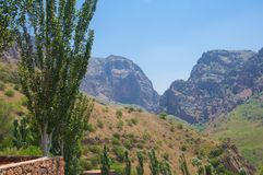 Vista do monastério de Noravank em montanhas vermelhas, em montes, em árvores de álamo e no céu azul Fotos de Stock