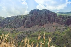 Vista do monastério de Noravank em montanhas vermelhas, em montes verdes e no céu azul arménia Fotos de Stock