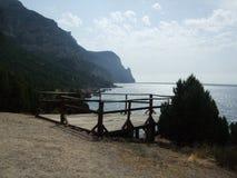 Vista do monte com os corrimão e o pinheiro da ponte de madeira no litoral o Mar Negro crimeia imagem de stock royalty free