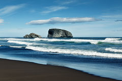 Vista do Oceano Pacífico, da ilha no oceano e da praia com a areia vulcânica preta Kamchatka, Extremo Oriente Imagens de Stock