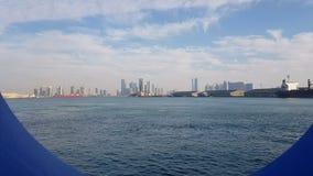 Vista do porto marítimo e do oceano azul em um dia ensolarado Vista do oceano azul através da vigia de um forro do cruzeiro video estoque