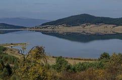 Vista do reservatório da represa de Batak, da clareira litoral do outono, da floresta com reflexão e dos montes em montanhas de R fotografia de stock