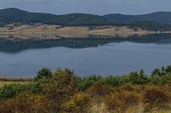 Vista do reservatório da represa de Batak, da clareira litoral do outono, da floresta com reflexão e dos montes em montanhas de R foto de stock