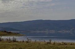 Vista do reservatório da represa de Batak com a clareira litoral do outono, floresta, monte nas montanhas de Rhodope e nos pássar fotografia de stock
