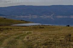 Vista do reservatório da represa de Batak com a clareira litoral do outono, floresta, monte nas montanhas de Rhodope e nos pássar fotos de stock
