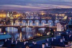 A vista do rio de Vltava e das pontes brilhou com o sol do por do sol, Praga Fotos de Stock