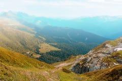 Vista do vale com grama e as árvores amareladas, cercada por montanhas altas na névoa em um dia do outono imagens de stock royalty free