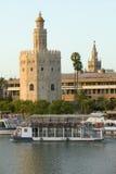A vista dos barcos da excursão e da torre octogonal de Torre del Oro faz a reflexão dourada em Canal de Alfonso de Rio Guadalquiv Fotos de Stock