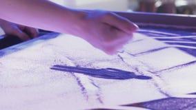 Vista dos dedos da mulher que tiram a imagem bonita da família pela areia Arte lighting video estoque