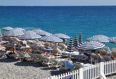 Vista dos guarda-chuvas e das cadeiras na praia em agradável Imagens de Stock Royalty Free