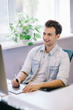Vista dos homens de funcionamento no escritório Desenhista à moda no assento do trabalho Centrado sobre seu trabalho Imagem de Stock