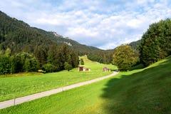 Vista dos prados alpinos bem arrumados com anexo e da estrada que estica na distância fotos de stock royalty free