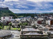 Vista dos telhados de Edimburgo com os penhascos de Salisbúria no fundo imagens de stock