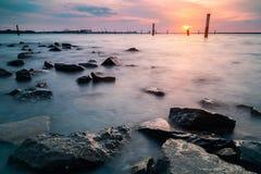 Vista dramática de la playa rocosa en Selangor durante puesta del sol fotografía de archivo