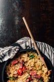 vista elevada de las pastas con el jamon, tomates de cereza, hojas de menta cubiertas por el parmesano rallado en cacerola con la foto de archivo libre de regalías