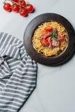 vista elevada de las pastas con las hojas de menta, el jamon y los tomates de cereza cubiertos por el parmesano en la placa en la imagen de archivo