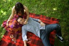 Vista elevada de los pares jovenes que se relajan en la hoja en parque Fotos de archivo