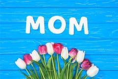 vista elevada del ramo de tulipanes y de mamá rosados y blancos de la palabra en la tabla azul, concepto del día de madres fotografía de archivo