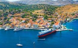 Vista em casas gregas tradicionais bonitas em montes verdes da ilha de Symi, porto marítimo do iate, ferryboat do turista na baía foto de stock royalty free