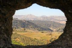 Vista em cima das planícies circunvizinhas de Ronda através de um furo rochoso Fotografia de Stock Royalty Free