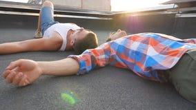 Vista em dois homossexual novos que encontram-se no telhado com luz solar brilhante no fundo Homens que descansam e que apreciam  vídeos de arquivo