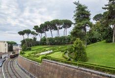 Vista em jardins do Vaticano com gramados e as árvores verdes bonitos, em estrada de ferro e em estação, Roma, Itália fotos de stock royalty free