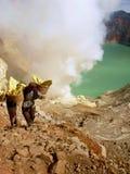 Vista em mineiros na cratera do vulcão de Ijen em Indonésia, em uma mina do enxofre e no gaz tóxico fotografia de stock royalty free