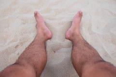 Vista em pares de pés humanos que encontram-se na areia Imagem de Stock Royalty Free