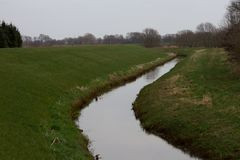 Vista em uma escavação enchida com água cercada por uma área da grama no emsland Alemanha do rhede imagens de stock royalty free