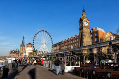 A vista em uma feira de divertimento com a roda de ferris gigante e o divertimento monta a Foto de Stock