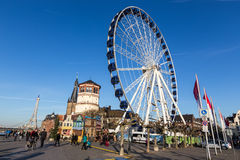 A vista em uma feira de divertimento com a roda de ferris gigante e o divertimento monta a Imagem de Stock