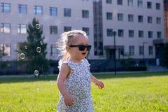 Vista em uma menina pequena bonito da criança nos óculos de sol no parque da cidade em um dia de verão ensolarado A menina tem o  foto de stock