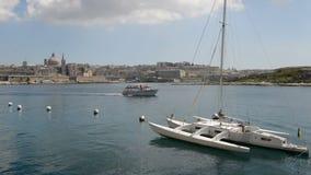 A vista em Valletta e a vela yacht com o iate ucraniano da bandeira e do cruzeiro com turistas filme