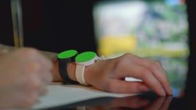 Vista enfocada de dos relojes blancos y negros con las pantallas verdes en mano izquierda del ` s de la muchacha almacen de metraje de vídeo