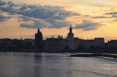 Vista escénica de la ciudad y del río viejos de Moldava durante salida del sol Edificios reflejados en agua El sol ocultado detrá fotografía de archivo