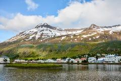 Vista escénica de la pequeña ciudad Seydisfjordur en Islandia del este en verano con el lago y la nieve fotos de archivo