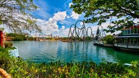 Vista escénica de los paseos de la montaña rusa a través del lago azul en los estudios universales de la Florida foto de archivo libre de regalías
