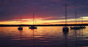 Vista escénica de yates silueteados contra colorido después de puesta del sol Foto de archivo libre de regalías