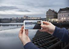 Vista escénica del centro histórico Praga, del puente de Charles y de edificios de la vieja mano de la ciudad con un smartphone,  foto de archivo